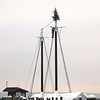 """Record-Eagle/Glenn Puit<br /> Brendan O'Donnel of the Traverse Tall Ship Co. labors to place a Christmas tree and lights at the top of the Manitou schooner at the Harbor West Marina on Grand Traverse Bay Monday morning. Company owner Dave McGinnis said placing a tree at the top of the tallest mast on a schooner is a long-time tradition """"and it's fun, too."""""""