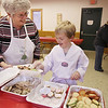 Record-Eagle/Keith King<br /> Joan Kroupa, chairperson of the Old Mission Women's Club Christmas cookie committee, helps her grandson, Samuel Kroupa, 8, of Old Mission Peninsula, as he selects cookies Saturday, December 8, 2012 during the 17th annual Old Mission Women's Club Christmas Cookie Sale at Peninsula Township Fire Hall #2 on Old Mission Peninsula. Funds raised from the event go toward local community and human services organizations.