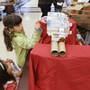 Record-Eagle/Keith King<br /> Anastasia Covert, left, of Traverse City, and her sister Isabella Covert, 7, see how many water bottles they can place to test the structural integrity of a bridge, constructed by the girls and their father, Doug Covert, at the 'Space Junk Station' Saturday, December 8, 2012 during Super Science Saturday at Traverse City Central High School. Profits from the event support FIRST Robotics Team 1711, The RAPTORS of Traverse City Central High School.