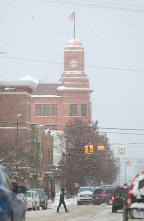 Record-Eagle/Keith King<br /> Snow falls Monday as traffic and pedestrians travel on Union Street in downtown Traverse City.