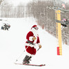 Record-Eagle/Keith King<br /> Santa skis Wednesday, Christmas Day, during the Ski Free with Santa event on Schuss Mountain at Shanty Creek Resorts in Bellaire. Donations of non-perishable food items, clothes and household items for the Father Fred Foundation were encouraged.