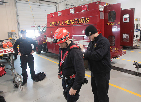 Record-Eagle/Keith King<br /> Jacob Garris, from left, firefighter and EMT, looks on as Curtis Walters, firefighter and EMT, has his harness looked at by Lt. Andy Doornbos as the group re-familiarizes themselves with confined-space gear Wednesday, Christmas Day, at Grand Traverse Metro Fire Department Station 1.