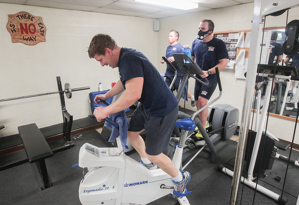 Record-Eagle/Keith King<br /> Tom Thompson, from left, Chris Peron and Ken Funk, all firefighters and paramedics, work out Wednesday, Christmas Day, at the Traverse City Fire Department Station 1. Funk, on far right, is wearing a mask which simulates high-altitude training.