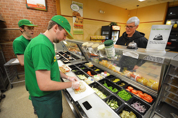 Record-Eagle/Dan Nielsen<br /> Subway employee Caleb LeBlanc builds a sandwich for Rick Simons, of Traverse City, at the restaurant chain's location near the corner of Hammond and Three Mile roads.