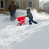 Jan-Michael Stump<br /> Noah Kirby, 4, helps his grandfather Paul Maxbauer clear snow in Traverse City's Central Neighborhood on Tuesday afternoon. Maxbauer said he regularly gets help from Kirby and his shopping cart-turned snowblower.