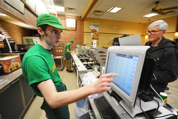 Record-Eagle/Dan Nielsen<br /> Subway employee Carl Schaub tallies up the total for Rick Simons, of Traverse City, who was buying sandwiches at the restaurant chain's location at the corner of Hammond and Three Mile roads.