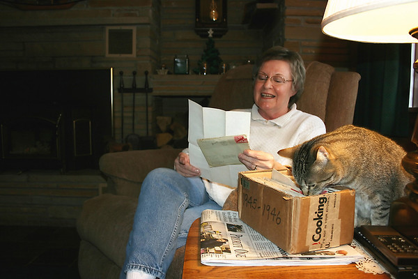 Record-Eagle/Loraine Anderson<br /> Cindy Pekkala's looks for a particular paragraph in one of her father's World War II letters while her curious tiger cat, Itty Bitty Kitty Cat, checks out one of the three boxes of war letters the family found after Jim Pekkala died in late 2008.
