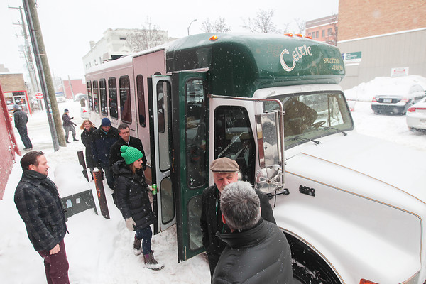 Record-Eagle/Keith King<br /> Passengers board a Celtic Shuttle and Tours bus as John O'Brien (in hat at lower right), owner, stands near Friday in Traverse City.