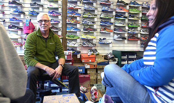 Record-Eagle/Nathan Payne<br /> Tim Hinkle talks to Sue Ballard and Diane Parker while the women try on new running shoes at Running Fit's downtown Traverse City location.