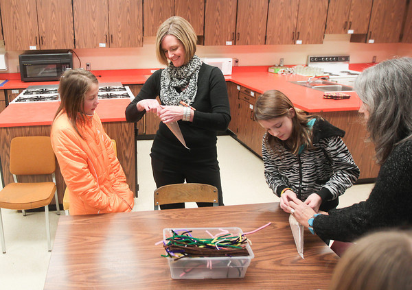 Record-Eagle/Keith King<br /> Amy Burk, executive director of the Communities In Schools of Mancelona after-school program, helps student Paige Schlaff, left, as Lillian-Anne Pickard, right, is assisted by Connie Brigham, far right, retired Mancelona fifth-grade teacher.