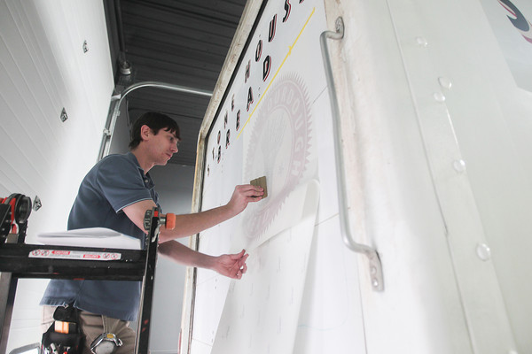 Record-Eagle/Keith King<br /> Eric Peterson, an employee at image360, prepares to apply a graphic on a box truck.
