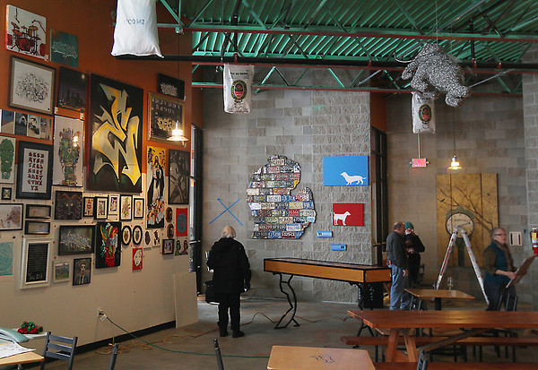 Record-Eagle/Keith King<br /> Art hangs from the walls of Right Brain Brewery Wednesday, January 2, 2013 as preparations are made for Grand Traverse Art Bomb scheduled for January 5 through March 30.