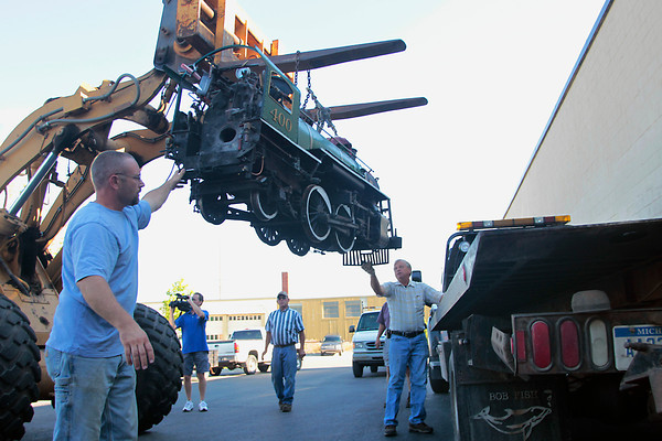 "Record-Eagle/Jan-Michael Stump<br /> Bill Fenton, left, and Glenn Arnold of the Northwest Michigan Engine and Thresher Club guide the Spirit of Traverse City as it is hoisted onto a truck to be transported to the site of the Buckley Old Engine Show Friday morning in Traverse City. The 2,770 pound train formerly ran at Clinch Park. Ward Eaton Towing provided the transporting truck for free. ""I want to keep it as safe as I can, this is my baby here,"" said Bancroft."