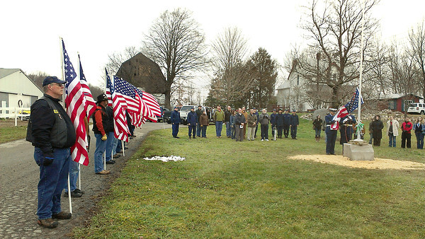Record-Eagle/Michael Walton<br /> Veterans, volunteers and their family members watch members of the U.S. Coast Guard Color Guard raise a flag over Reining Liberty Ranch on Dec. 17.