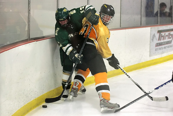 Record-Eagle/Keith King<br /> Traverse City West's John MacLellan, left, tries to get the puck against Traverse City Central's Ian McGraw.