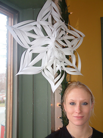 Record-Eagle/Marta Hepler Drahos<br /> Heather Kordish stands beneath one of the paper snowflakes she folded and cut to decorate Stone House Bread in Leland. The craft became popular in the Victorian era.