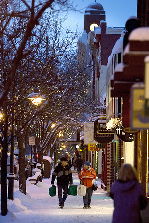 Record-Eagle/Keith King<br /> Pedestrians travel as lights illuminate the sidewalk in downtown Traverse City.