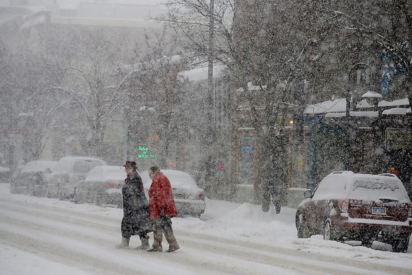 Record-Eagle/Keith King<br /> Pedestrians cross Front Street as snow falls in downtown Traverse City.
