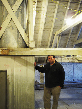 Record-Eagle/Bill O'Brien<br /> Bob Jacobson is shown in the attic of Building 50 at the former state hospital grounds next to one of its spires that extends to the roof. The space will be part of a 39-unit affordable housing project that's under construction.