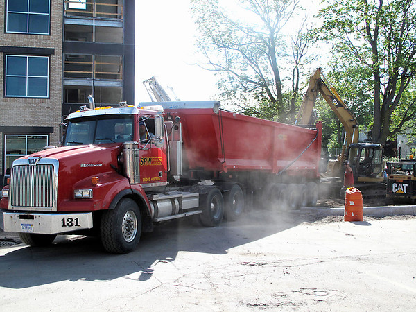Record-Eagle/Bill O'Brien<br /> A work crew from SRW Contracting Paving is completing site work at Traverse City's new parking deck in Old Town while lawsuits pile up against the company.