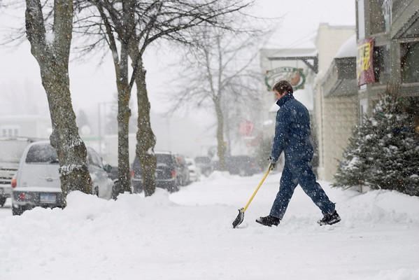 Record-Eagle/Keith King<br /> Jordan Newcomb, 18, shovels snow from the sidewalk in front of Edward's Home Furnishings, where he works, in Suttons Bay.
