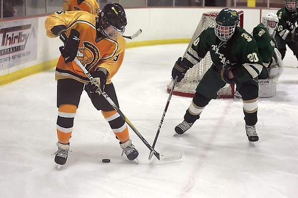 Record-Eagle/Keith King<br /> Traverse City Central's Marcus Russell tries to protect the puck against Traverse City West's David Dudley in Howe Arena at the Grand Traverse County Civic Center.