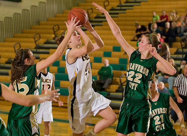Record-Eagle/Jan-Michael Stump<br /> Grand Haven's Sarah Krober (44) drives to the basket between Traverse City West's Shaina Streeter (15) and Ressa Borkovich (22) in the first half of Saturday's game.