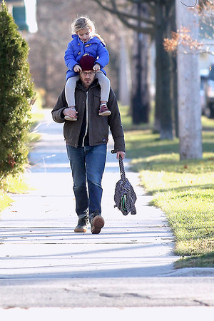 Record-Eagle/Jan-Michael Stump<br /> Madeline Jonas, 5, plays with the glasses of her father, Gary Jonas, as he carries her home from school in Traverse City's Central Neighborhood.