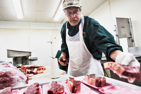 "Record-Eagle/Pete Rodman<br /> Resident ""protein artist"" Jerry Deering cuts new york strip steaks at Deering's Market and Deli at 827 Union St. on Thursday. Deering said it was natural for beef prices to rise a little during the holiday season, but beef prices had a major rise last summer."