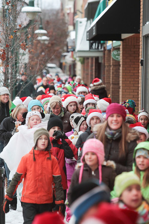 Record-Eagle/Keith King<br /> Immaculate Conception Elementary School students, soon to be joined by Holy Angels Elementary School students, walk along Front Street Friday to donate toys to Traverse City Fire Department firefighters and paramedics as part of the Traverse City Fire Department toy program. After students donated toys they watched short holiday films at the State Theatre.