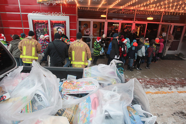 Record-Eagle/Keith King<br /> Toys are donated by students Immaculate Conception Elementary School and Holy Angels Elementary School Friday for the Traverse City Fire Department toy program. After the toy donations students watch short holiday films at the State Theatre.