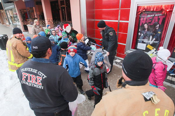 Record-Eagle/Keith King<br /> Traverse City Fire Department firefighters and paramedics collect toy donations from Holy Angels Elementary School students at the State Theatre Friday for the Traverse City Fire Department toy program. Immaculate Conception Elementary School students also donated toys. After the students donated toys they watched short holiday films at the State Theatre.