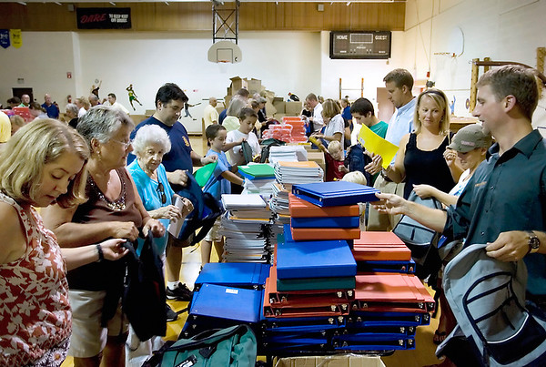 Record-Eagle file photo/Keith King<br /> Volunteers place school supplies into backpacks last summer at Oak Park Elementary School as part of the Traverse Bay Sunrise Rotary Club Backpacks for Kids project. Another Backpacks for Kids fund-raising event -- a snowshoe hike -- is scheduled for Saturday.