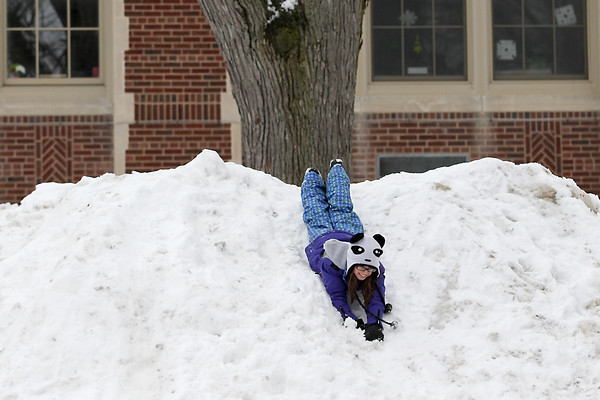 Record-Eagle/Jan-Michael Stump<br /> Amanda Solem, 10, and Ella Lamb, 8, (not pictured) play on a snow hill outside Central Grade School in Traverse City on Monday after school.