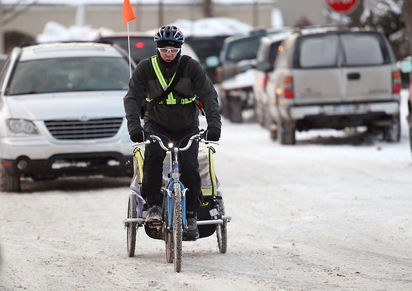 Record-Eagle/Keith King<br /> Ross Hammersley, of Traverse City, pedals his bike as his son, Emerson Hammersley, 6, rides in a bike trailer Wednesday, February 6, 2013 as Ross takes his son to school. Afterward Hammersley continues riding his bike as he commutes to work.