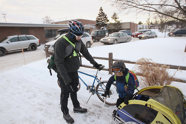 Record-Eagle/Keith King<br /> Ross Hammersley, of Traverse City, stands near as his son, Emerson Hammersley, 6, exits a bike trailer he was riding in Wednesday, February 6, 2013 as Ross drops him off at school. Afterward Ross continues riding his bike as he commutes to work.