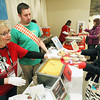 Record-Eagle/Keith King<br /> Volunteer Donna Valdmanis, left, near Zachery White, manager of The Kitchen, hands a cup of buffalo chicken soup with bacon focaccia and blue cheese crumbles to Meredith Nichol, right, of Traverse City, during the Soup'r Bowl Saturday, February 16, 2013 during the Traverse City Winter Comedy Arts Festival.