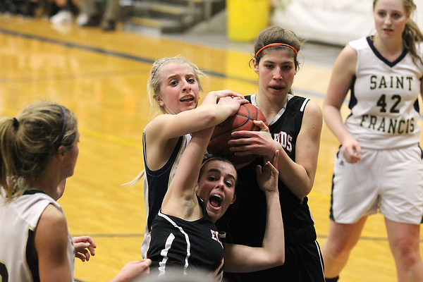 Record-Eagle/Jan-Michael Stump<br /> Elk Rapids' Michelle Costa (10) calls for a foul while fighting for a rebound with Paige Granger (40) and Traverse City St. Francis' Kenzie Feeney (4) in the second half of Monday's game.