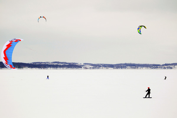 """Record-Eagle/Keith King<br /> Daniel Andrews, bottom right, of Traverse City, as well as others, snowkite Wednesday on East Grand Traverse Bay. An upcoming area event called the 2014 Midwest Snow Kite Jam is scheduled for February 14-17. For more information visit  <a href=""""http://www.facebook.com/2014snowkitejam"""">http://www.facebook.com/2014snowkitejam</a>."""