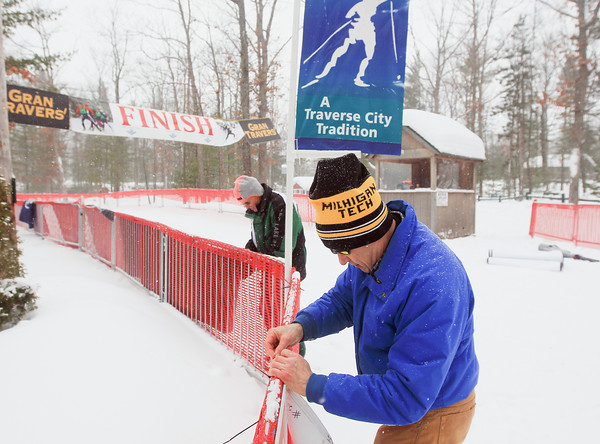 Record-Eagle/Keith King<br /> Jim Woodburne, back, and Michael Tarnow, both North American Vasa board members, hang sponsor banners near the finish line as preparations are made for the 38th annual Vasa Festival of Races at Timber Ridge Resort.