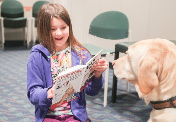 """Record-Eagle/Keith King<br /> Lindsey Greenfelder, 8, of Traverse City, reads """"Bad Kitty: The Uproar at the Front Door,"""" by Nick Bruel, to CeCe during the Tell-A-Tail program at the Traverse Area District Library Woodmere Avenue branch in Traverse City. The program is also scheduled to take place February 21 and March 21 at 4:00 p.m."""