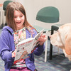 "Record-Eagle/Keith King<br /> Lindsey Greenfelder, 8, of Traverse City, reads ""Bad Kitty: The Uproar at the Front Door,"" by Nick Bruel, to CeCe during the Tell-A-Tail program at the Traverse Area District Library Woodmere Avenue branch in Traverse City. The program is also scheduled to take place February 21 and March 21 at 4:00 p.m."