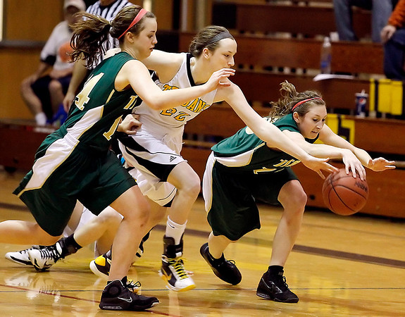 Record-Eagle/Jan-Michael Stump<br /> Traverse City West's Lauren Ellison (14) and Shaina Streeter (15) chase down a loose ball with Traverse City Central's Molly Walker in the third quarter of Thursday's game.