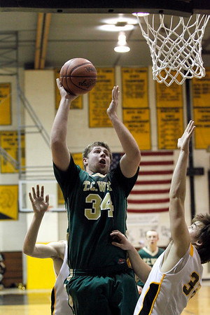 Record-Eagle/Jan-Michael Stump<br /> Traverse City West's Julius Moss (34) puts up a shot over Traverse City Central's Mack Sovereign.