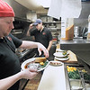 Record-Eagle/Jan-Michael Stump<br /> John Larbarbera, left,  and Joe Kolarovic prepare meals in the kitchen at Mode's Bum Steer on Wednesday. The restaurant is offering a number of specials, including ribs, prime rib, lettuce wedge and bananas foster as specials during restaurant week.