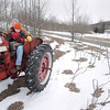 "Record-Eagle/Keith King<br /> Jason Bancroft, of Solon Township, along with his son, Isaac, 6, drives his 1959 Farmall tractor toward his house Friday after visiting a neighbor. ""We were over bugging the neighbor,"" Jason said."