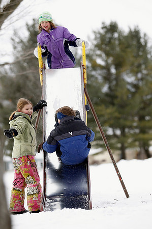 Record-Eagle/Jan-Michael Stump<br /> Anneliese Ferguson, 7, left, and Zoe Bolde, 7, top, watch Zak Bolde, 7, slide backwards on a slide at F&M Park. There is a chance of more snow this weekend.