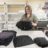 Record-Eagle/Keith King<br /> Katie Hauser, executive housekeeper, folds garments, donated by Traverse Bay Manufacturing, after they were dried in machines at Cambria Suites in Traverse City. The garments became wet when a pipe froze and burst at Traverse Bay Manufacturing. Cambria Suites volunteered to launder the garments which are planned to be donated to The Father Fred Foundation once they're washed, dried and folded.