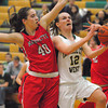 Record-Eagle/James Cook Traverse City West's Kiley Kreple (12) drives past Marquette's Elizabeth Kurin (40) in Wednesday's Class A district semifinal at West. The Titans won 42-39 and will host Friday's district final.