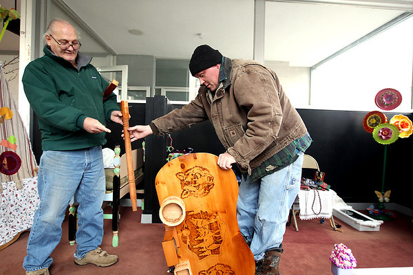 Record-Eagle/Keith King<br /> Ray Walenter, left, hands a wooden desk leg to his stepson, Tom Stebbins, both of Interlochen, as Stebbins assembles the desk in the building at the northeast corner of Cass Street and Front Street in Traverse City Wednesday, February, 27, 2013 as preparations are made for Goodwill's Reinvention Convention art sale and competition. A gala for the event is scheduled for Friday from 6:00 p.m. until 10:00 p.m. with tickets costing $30. A public viewing is scheduled for Saturday from 9:00 a.m. until 6:00 p.m. The art pieces are made using store items from Goodwill. The desk is in the name of Walenter's wife, Nancy Walenter, who did the wood burning. Ray Walenter used a scroll saw on the desk's wooden baskets while Stebbins stained, sanded and assembled the desk.